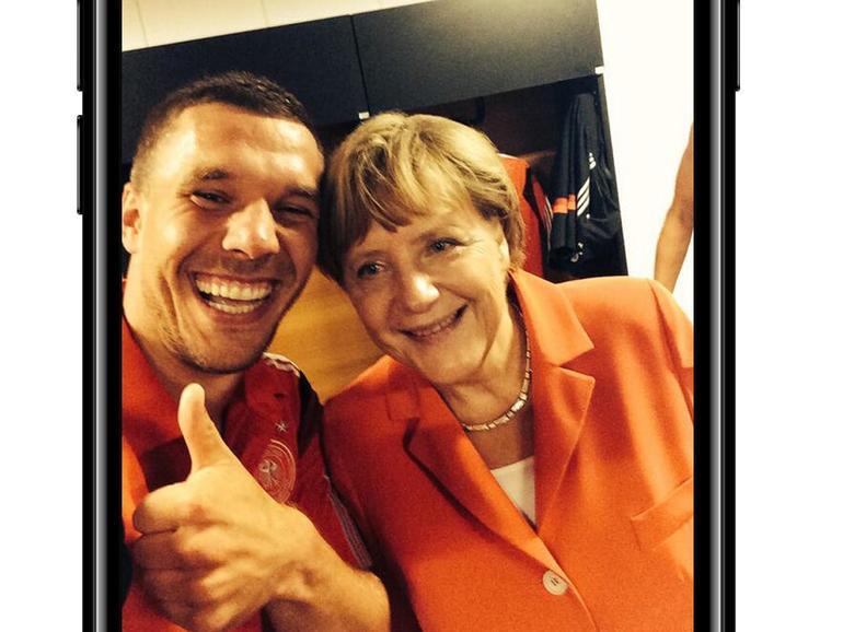 Nach dem WM-Auftaktsieg gegen Portugal posiert Merkel in der deutschen Kabine mit der Mannschaft und wird danach zwanglos von Lukas Podolski am ausgestreckten Arm abgelichtet.