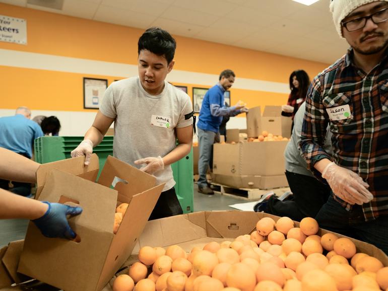 Apple-Mitarbeiter sortieren Orangen in der Second Harvest Food Bank in San Jose, Kalifornien.