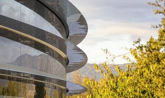 Gedankenverlorene Apple-Mitarbeiter laufen am Apple Campus vor Scheiben